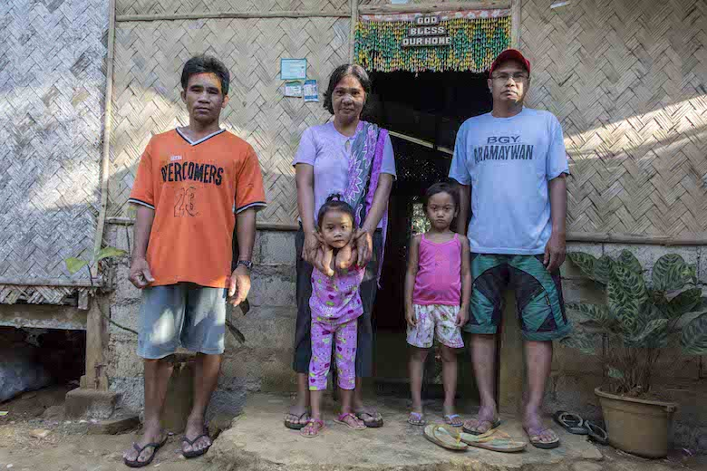 Pasteur Montalib Kamil (right), stands with his familly outside the family house in Aramaywan village. He is a tribal leader of the Tagbanuwa tribe in the municipality of Quezon and works with the NGO coalition Ancestral Land Domain Watch (ALDAW). Photo by Rod Harbinson.