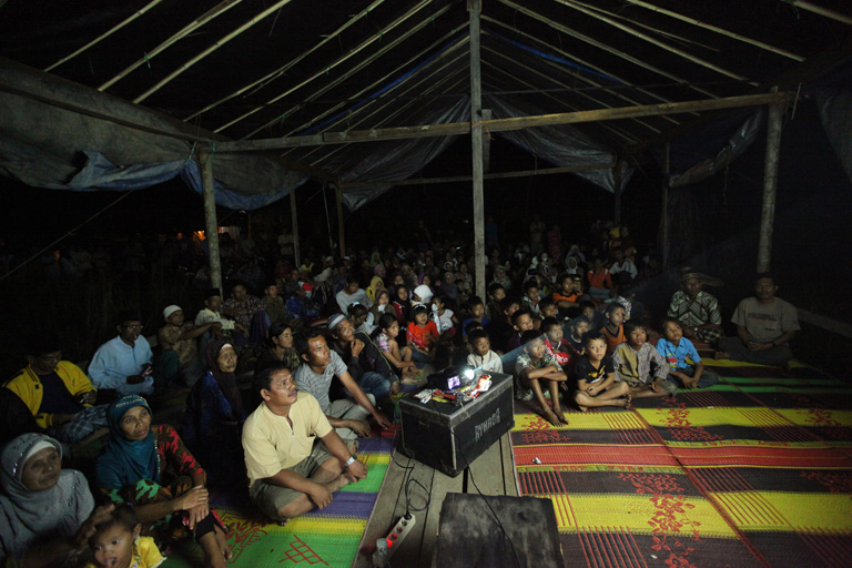 A community in Senyerang, Indonesia watches the Territories of Life series. Photo courtesy of LifeMosaic.
