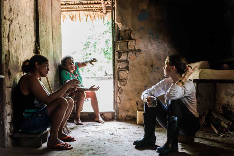 Biologist Raquel Rodrigues Santos (right) and anthropologist Natália Guerrero (left) talk to a beiradeira, Cleunisa Neves da Silva. The team's report to the Brazilian courts will help determine if 15 families can stay on Amazon basin lands they first settled during the World War II era. A newly declared ecological station could push them out. Photo by Sue Branford