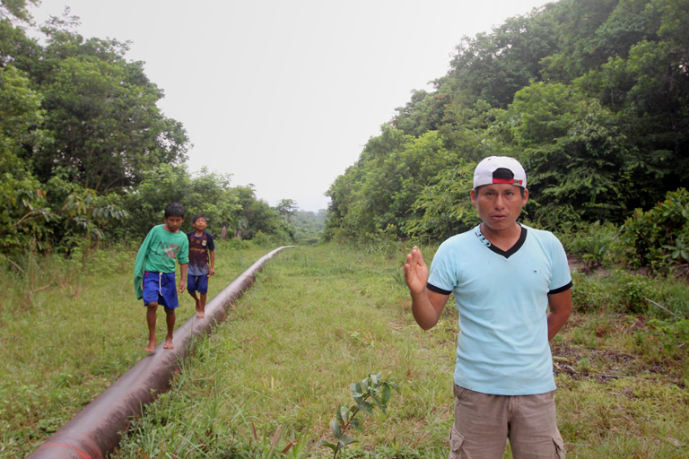 Elías Wasún, apu or president of the Wampis community of Mayuriaga, stands beside the pipeline where it passes just meters from houses. A spill about 13 km from the village affected more than 20 communities along the Morona River. Photo by Barbara Fraser.