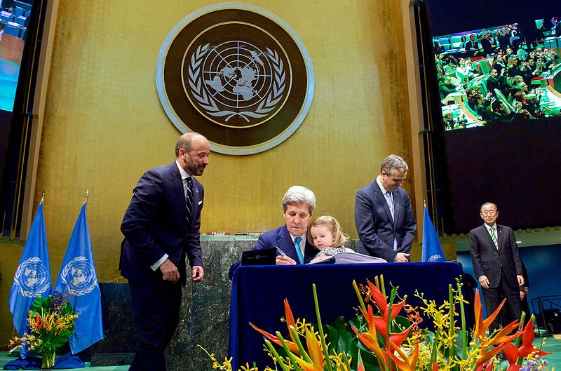 US Secretary of State John Kerry signs the Paris Agreement at the UN in New York while holding granddaughter Dobbs Higginson on his lap. Scientists warn that the agreement is insufficient to prevent disastrous climate change. Photo courtesy of US Department of State.