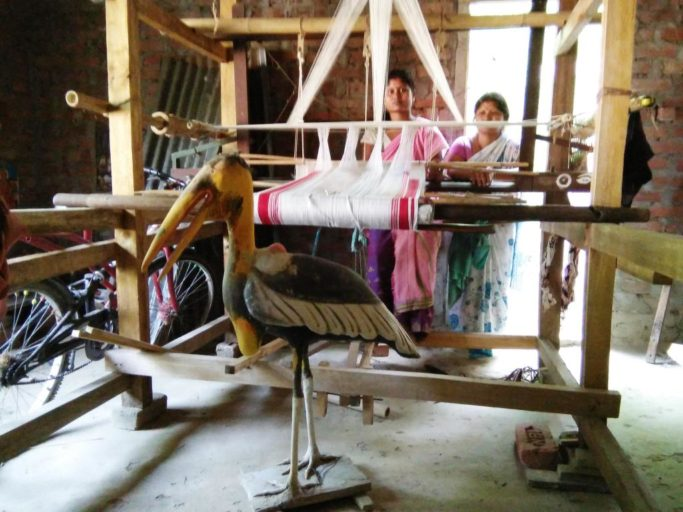 Members of the self help weaving group with Greater Adjutant statue and handloom donated by the government. Photo by Purnima Barman