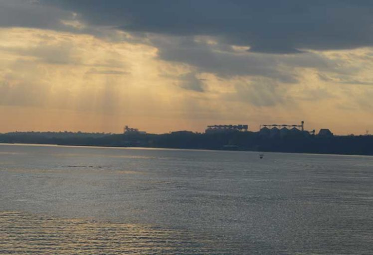 An early morning view of the grain silos on the eastern bank of the Tapajós River, directly across from the city of Itaituba. These silos at a newly built river port are an indicator of the rapid industrialization of the region, as road, rail and waterway infrastructure is built to support the export of soy and other commodities from Mato Grosso state. Small-scale gold miners and indigenous people are worried about this large-scale infrastructure development, and could end up becoming uneasy allies because of it. Photo by Zoe Sullivan for Mongabay.